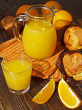Fresh orange juice and muffins. On a wooden table Royalty Free Stock Photography
