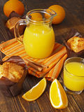 Fresh orange juice and muffins. On a wooden table Stock Image