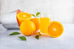 Fresh orange juice and orange in a basket on a white wooden bac stock image