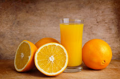 Fresh orange juice and oranges Stock Photography