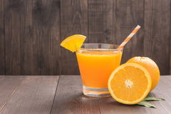 Fresh orange juice and oranges on wooden table Stock Images
