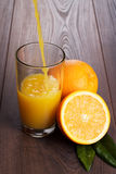 Fresh orange juice pouring into glass on the table Royalty Free Stock Image