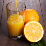 Fresh orange juice pouring into glass on the table Stock Images