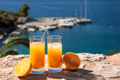 Fresh orange juice summer soft drink concept. Fresh orange juice with ice, oranges on a stone surface by the seascape view summer soft drink concept. Horizontal Stock Photo