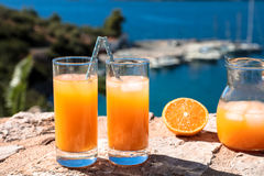 Fresh orange juice summer soft drink concept. Fresh orange juice with ice, oranges on a stone surface by the seascape view summer soft drink concept. Horizontal Royalty Free Stock Photography