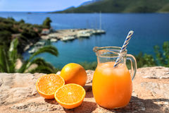 Fresh orange juice summer soft drink concept. Fresh orange juice with ice, oranges on a stone surface by the seascape view summer soft drink concept. Horizontal Royalty Free Stock Photos