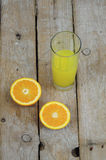 Fresh orange juice and two halves of a fruit. On wooden table Stock Photo