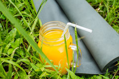 Fresh  orange juice and yoga mat on the grass Stock Images