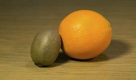 Fresh orange and kiwi on a wooden surface royalty free stock photos