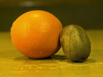 Fresh orange and kiwi on a wooden wet surface Royalty Free Stock Photography