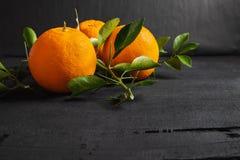Fresh orange and leaf on black background royalty free stock photography