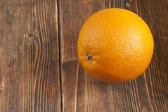 Fresh orange lying on the board. Orange lies on the old board Royalty Free Stock Image