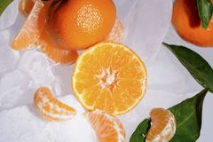 Fresh orange mandarin fruit with green leaves are frozen on cold blue ice. Stock Photos