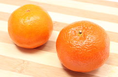 Fresh and orange mandarins on wooden background Royalty Free Stock Photography