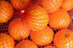 Fresh orange oranges in plastic netting. In Market. Food background texture Royalty Free Stock Photography