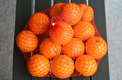 Fresh orange oranges in plastic netting. In Market. Food background texture Stock Images
