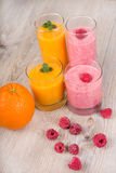 Fresh orange and raspberry smoothie drinks. On wooden background Royalty Free Stock Image