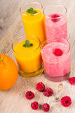 Fresh orange and raspberry smoothie drinks. On wooden background. Healthy bio organic vegan drink Stock Photos