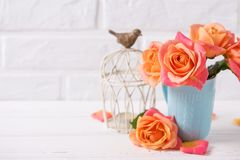Fresh orange roses in blue cup ans candle on white wooden backg. Round against brick wall. Place for text. Floral still life stock photography