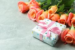 Fresh orange roses with gift and space for text on grey background. Closeup royalty free stock photos