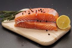 Fresh orange salmon steak surrounded by lemon, spices and herbs on a wooden board. stock photos