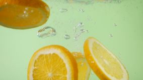 Fresh orange sliced falling in water with splash. On green background stock footage