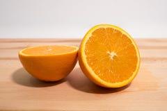 Fresh orange sliced in half on wooden board. Close up side view. Fresh orange sliced in half on wooden board. Close up side view with shallow depth of field stock photos