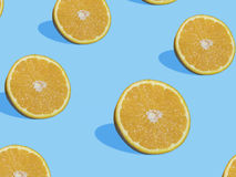Fresh orange slices on blue background with shadow , top view Royalty Free Stock Images
