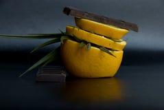 Fresh orange slices with chocolate in a dark background stock photos