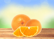 Fresh orange and slices on wooden table over nature background Royalty Free Stock Photos