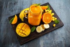 Fresh Orange smoothie drink with banana, mango on black wooden board. Stock Photos