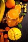 Fresh Orange smoothie drink with banana, mango, carrots on black wooden board. Stock Photos