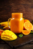 Fresh Orange smoothie drink with banana, mango, carrots on black wooden board. Royalty Free Stock Images