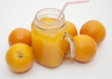 Fresh orange smoothie drink. Fresh smoothie drink with a straw surrounded by ripe oranges Stock Photo
