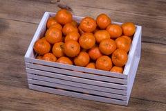 Fresh orange, tangerine fruit, mandarin pattern background in a wooden box . Concept of healthy, organic, vegan food Stock Photos