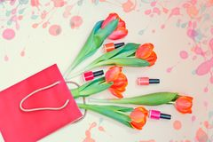 Fresh orange tulip flowers and nail polishes in paper bag. On beige background. Top view with copy space Stock Photo