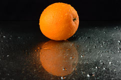 Fresh orange on a wet black background. Wet orange on a black background Royalty Free Stock Photos