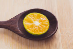 Fresh orange in a wooden spoon. With wooden background Royalty Free Stock Images