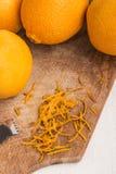 Fresh orange and zester to obtaining orange zest on an old woode Stock Photography