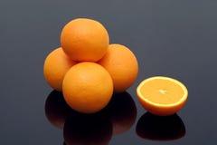 Fresh oranges. On black reflective background royalty free stock photos