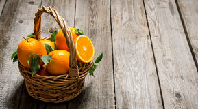 Fresh oranges in the basket with leaves. Stock Image