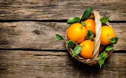 Fresh oranges in the basket with leaves. Stock Photo
