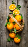 Fresh oranges in the basket with leaves. Royalty Free Stock Images