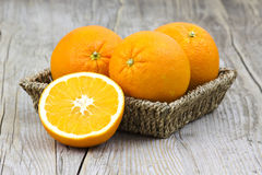 Fresh oranges in a basket. On old wooden background stock photo