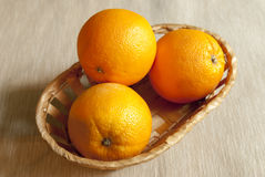 Fresh oranges in the basket. Three ripe oranges in the basket standing on the table Royalty Free Stock Images