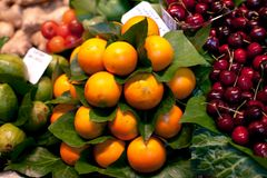 Fresh,oranges and cherries in greenery at a local farmers market in Barcelona Spain. Counter with heap of berries. stock photo