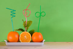 Fresh oranges with colorful fancy straw Stock Images