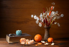 Fresh oranges and dried flowers in a vase Royalty Free Stock Photo