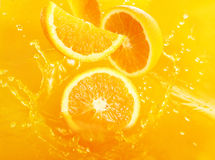 Fresh oranges falling in juice Royalty Free Stock Image