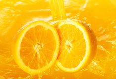 Fresh oranges falling in juice Royalty Free Stock Photo